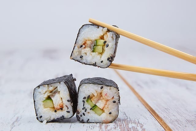 holding a sushi using wooden chopsticks