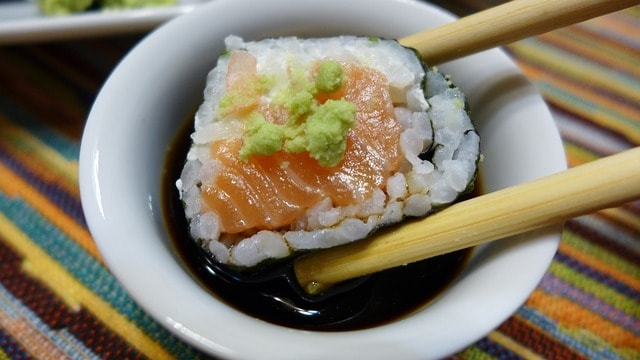 sushi dipped into soy sauce using wooden chopsticks