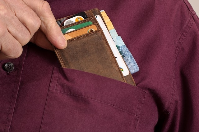 putting wallet with business cards in shirt pocket